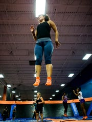 Devon White spins in the air as she leads a trampoline aerobics class at Skyzone in Newark on Wednesday evening.