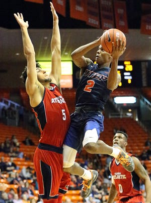 Omega Harris, 2, of UTEP drives for the basket against William Pfister of Florida Atlantic in the second half of their game Saturday night in the Don Haskins Center. The Miners won 66-65 in overtime.