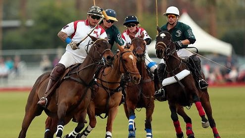 Polo player Kimo Huddleston (4, left) of team M3 Strolling Wild and his horse push past the pack including teammate Madelyn Cobb (2, white) and Lazy 3 players Issy Wolf (2, green) and Loreto Natividad (3, green) to get a lead toward the ball while playing team Lazy 3 in a five chukker match on Sunday, January 4, 2015 at Empire Polo Club in Indio.