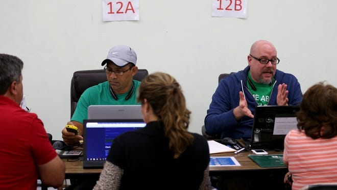 Ronald Sagarra (L) and Jose Alvarez, agents from Sunshine Life and Health Advisors, discuss plans available from the Affordable Care Act to customers at a store setup in the Mall of the Americas on December 15, 2014 in Miami, Florida. It was the last day for people to sign up if they want insurance coverage under the Affordable Care Act to begin January 1, 2015.