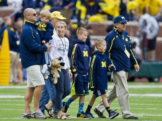 Former Michigan coach Lloyd Carr, far right, leads his grandsons T.J. and Tommy Carr, daughter-in-law Tammi Carr, and son Jason Carr, far left, holding his ailing son Chad Carr, onto the Michigan Stadium field for the pregame coin toss, before the win over Oregon State in Ann Arbor.