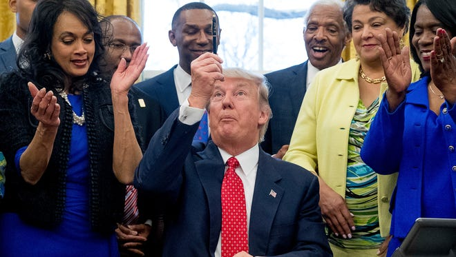 President Donald Trump holds up his pen after signing the Historically Black Colleges and Universities HBCU Executive Order, Tuesday, Feb. 28, 2017, in the Oval Office in the White House in Washington. (AP Photo/Andrew Harnik)