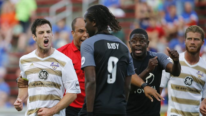 Louisville City FC midfielder Paolo Delpiccolo (36), left, is restrained by the referee as he exchanges words with FC Cincinnati forward Djiby Fall (9) in the first half during the Lamar Hunt US Open Cup game between Louisville City FC and FC Cincinnati Wednesday at Nippert Stadium.