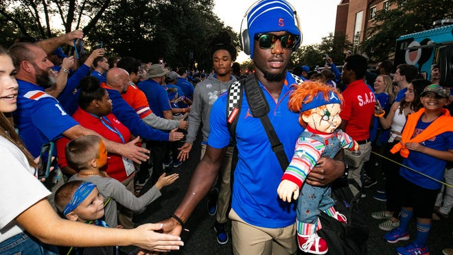 Florida defensive back Kaiir Elam gives low-fives to fans as he carries the Chucky doll during Gator Walk on Nov. 30, 2019 at Ben Hill Griffin Stadium.
