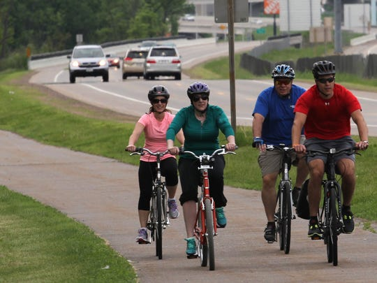 Carrie Hutton, from left, Laura Scudiere, and local biking enthusiasts Denny Helke and Aaron Ruff, bike June 5 on the trail along Highway R in Wausau.