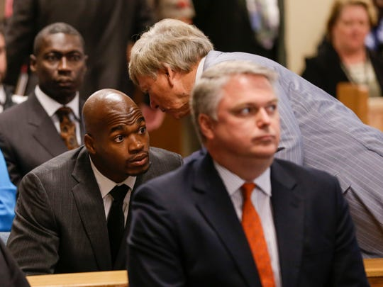 Adrian Peterson listens to his attorney Rusty Hardin in the Montgomery county courthouse courtroom during his arraignment, Oct. 8, 2014.