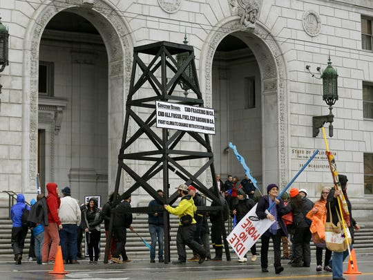 Protesters prepare to take down a makeshift oil derrick that was set up in front of the California State Office Building to protest fracking in San Francisco on Friday.