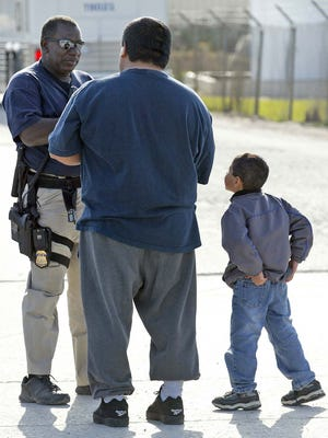 Eli Rodriguez, center, talks with an Immigration and Customs Enforcement officer outside Agriprocessors in Postville May 12, 2008, as his nephew, Kevin Rodriguez-Jimenez, 6, listens. Eli was asking about Kevin's mother, an undocumented worker at the plant.