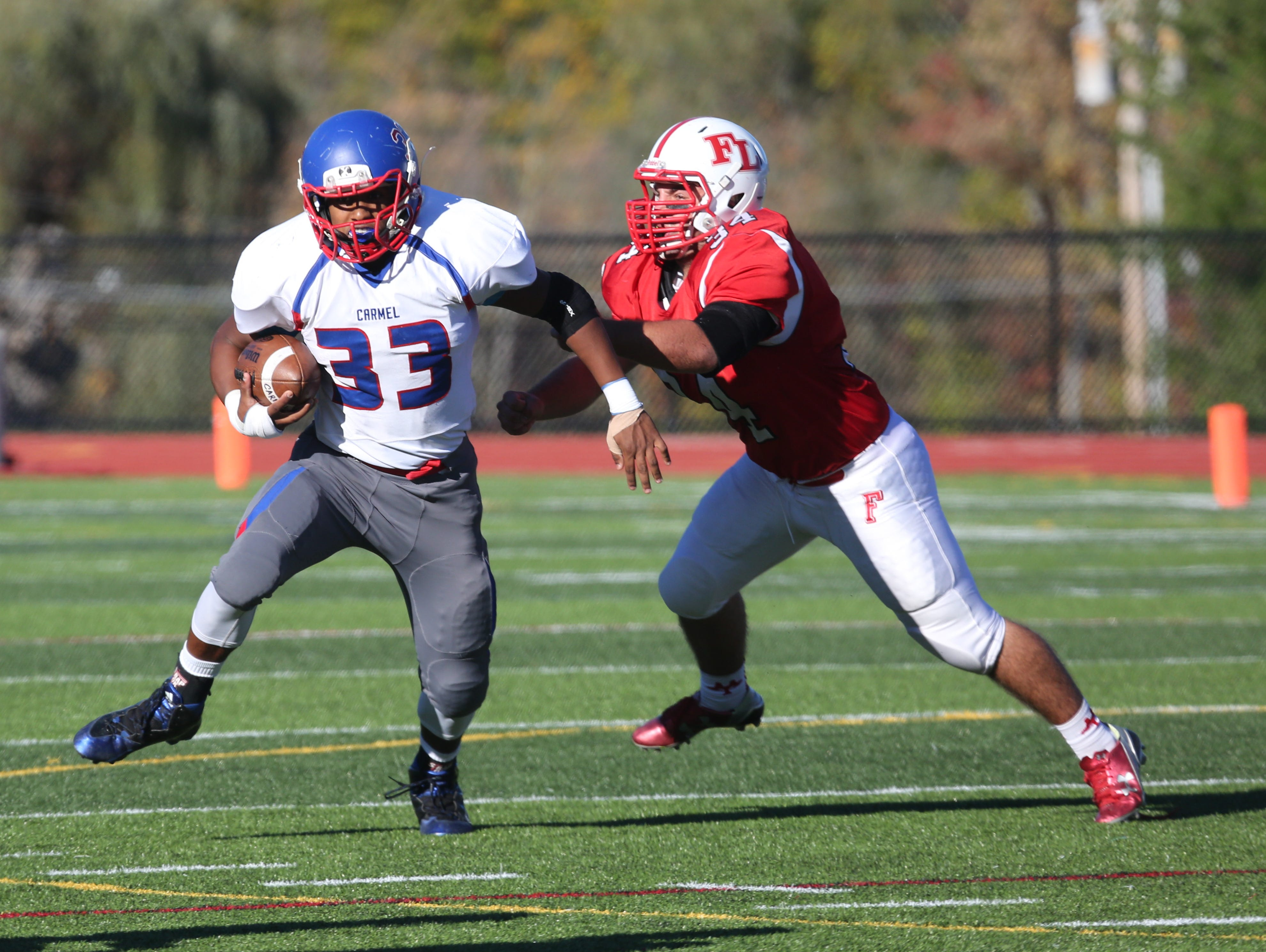 Carmel's John A. Morris III breaks away from Fox Lane defender Nick Cerutti during their game in Bedford, Oct. 10, 2105.