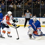 Rangers goaltender Cam Talbot (right) deflects a shot by Florida's Dave Bolland (63) as Bolland is checked by Rangers' Derick Brassard.