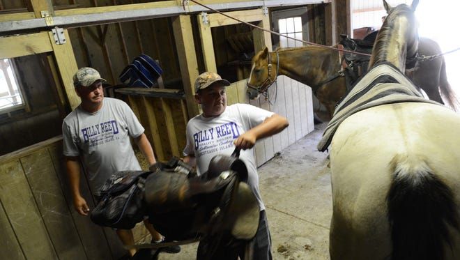 Billy Reed III, 14, saddles his horse Comet while his father looks on at their barn on Chincoteague Island, Va. on Saturday, July 23, 2016. The Reeds were preparing to trailer their horses to Assateague for the annual South Herd Roundup on Saturday. This year three generations of Reeds, all named Billy, will ride in the 91st Annual Chincoteague Pony Swim.