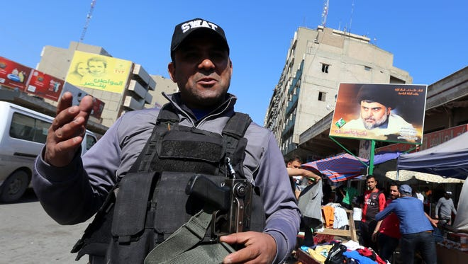 A member of the Iraqi security forces stands guard at a street market in central Baghdad  on Feb. 29, 2016.