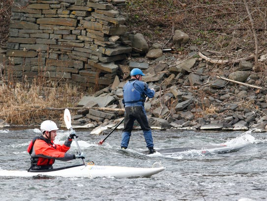 From left, Glenn Miga and Steve Bush ride a stationary wave on the Chenango River in Chenango Forks on Monday, December 4, 2017.