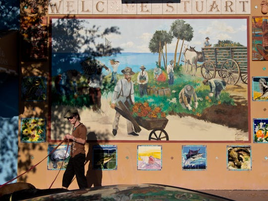 """Maureen Deighan, who has lived in Stuart for 35 years, walks her labradors Belle and Rose past a 2003 mural by Maureen Fulgenzi on Tuesday, Nov. 22, 2016, along Southwest Flagler Avenue in downtown Stuart. """"I was on the board of Main Street when there wasn't anything (downtown)...and now it's just wonderful,"""" she said. """"I just hope the (passenger) train doesn't come through and wreck everything."""""""