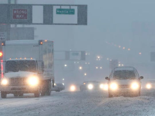 Vehicles drive drive through snow as they approach the Holland Tunnel, Thursday, Feb. 9, 2017, in Jersey City, N.J. A powerful, fast-moving storm swept through the northeastern U.S. early Thursday, making for a slippery morning commute and leaving some residents bracing for blizzard conditions.