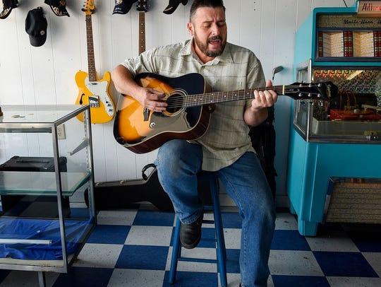 Steven Jackson, owner of Jacksons Barber Shop, plays