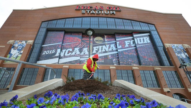 Workers from Ski Landscape work on putting fresh mulch around the flower on the north end of Lucas Oil Stadium Monday morning. Indianapolis is starting to polish up by getting ready for the thousands of people coming to town for the NCAA Final Four on April 4th & 6th.