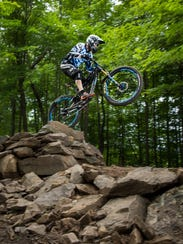 A mountain biker takes to the air on the advanced trail