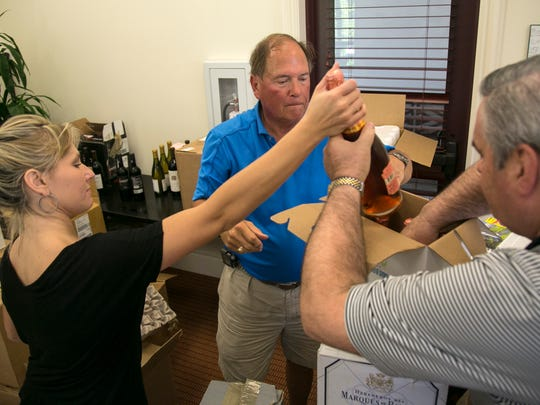 Melissa Cofta, left, Dick Swennumson and Bill Toler put together one of the wine auction lots on Wednesday at Miromar Lakes Beach & Golf Club. The wine will be auctioned off on Saturday at the Southwest Florida Wine & Food Fest.