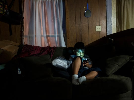 Jack Paz-Cruz, 7, a Pinewoods Elementary School student plays video games at his Bonita Springs home on Wednesday. He and his family were rendered homeless after an August storm and Hurricane Irma damaged their trailer and ruined their belongings. They stayed at a shelter for almost two months.
