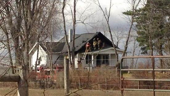 Firefighters assess the situation from the porch roof.