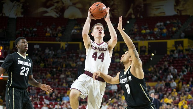 ASU guard Kodi Justice puts up a shot as Colorado's Askia Booker defends and Colorado's Jaron Hopkins (23) looks on during the first half of the PAC-12 college basketball game at Wells Fargo Arena in Tempe on Jan. 17, 2015.