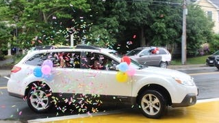 Confetti is thrown from a car during the graduation parade for Proctor School 6th-graders.