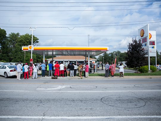 People congregate at the crime scene tape cordoning off a Shell gas station near 34th Street and Sherman Drive where a man was gunned down next to the pumps on Aug. 31.