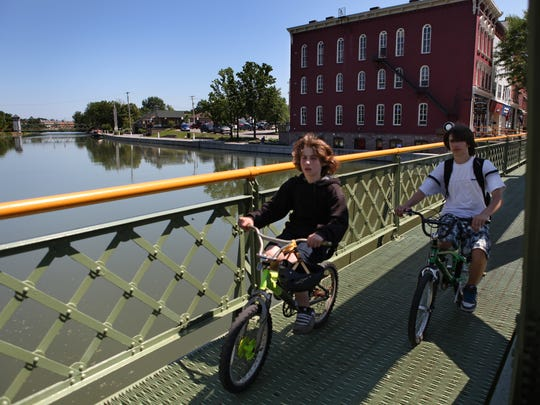 Forrest Macaluso, left, and Severin Ibarluzea (cq), right, ride their bikes on the Main Street bridge over the Erie Canal in Brockport. The village of Brockport has won the 2009 statewide award for promoting the canal from the Erie Canalway National Heritage Corridor.  The village's Welcome Center can be seen in the distance at to the left of the red building. The boys are from Brockport.  FOR OT  (Democrat and Chronicle, Photo by Annette Lein, 062409)
