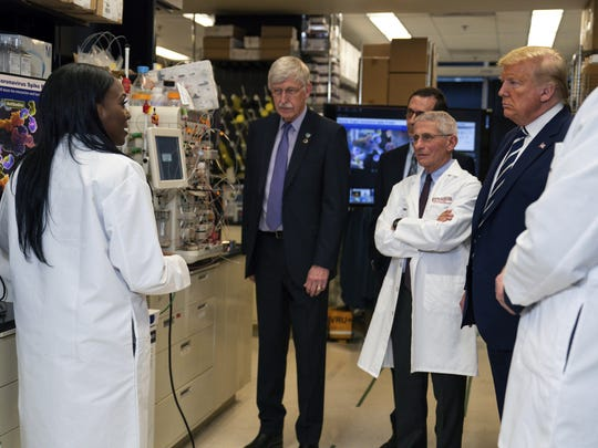 FILE - In this Tuesday, March 3, 2020 file photo, Dr. Kizzmekia Corbett, left, senior research fellow and scientific lead for coronavirus vaccines and immunopathogenesis team in the Viral Pathogenesis Laboratory, talks with President Donald Trump as he tours the Viral Pathogenesis Laboratory at the National Institutes of Health in Bethesda, Md. Dozens of research groups around the world are racing to create a vaccine as COVID-19 cases continue to grow. (AP Photo/Evan Vucci)