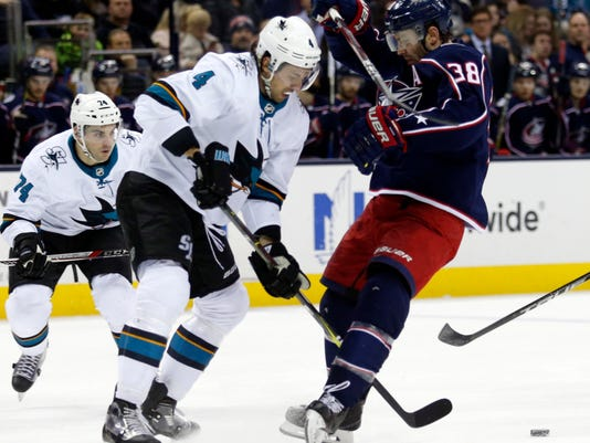 San Jose Sharks defenseman Brenden Dillon reaches for the puck on the other side of Columbus Blue Jackets forward Boone Jenner during the second period of an NHL hockey game in Columbus, Ohio, Friday, Feb. 2, 2018. (AP Photo/Paul Vernon)