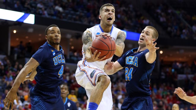 Florida Gators guard Scottie Wilbekin (5) drives to the basket against UCLA Bruins guard Norman Powell (4) and forward Travis Wear (24) during the first half in the semifinals of the south regional of the 2014 NCAA Mens Basketball Championship tournament at FedExForum.