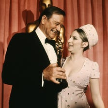 Hollywood, UNITED STATES: In this 1969 photo, US actor John Wayne accepts his Best Actor Oscar from US singer and actress Barbara Streisand.