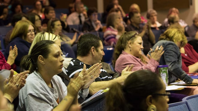 The audience claps as a resident voices concern about the recommended school closings at the special meeting of the Board of Education on Monday night.