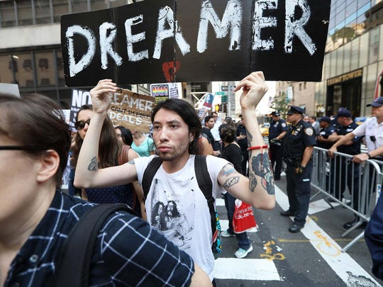 Joban Rodriguez, 27, holds a sign as he walks past Trump Tower and a line of police officers. Rodriguez, of Brooklyn, originally came to the U.S. at the age of 3. Tuesday, September 5, 2017