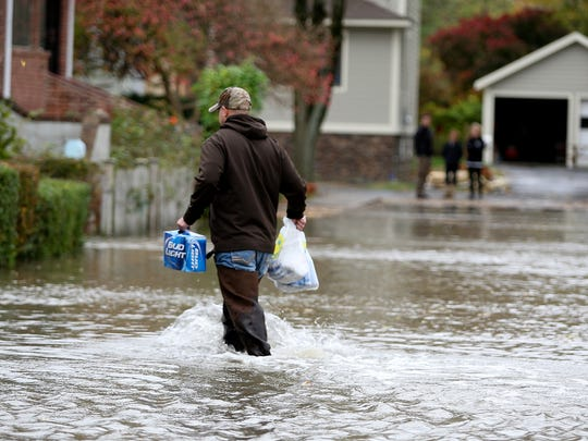With hurricane Sandy approaching a Piermont resident wades through the rising waters at the corner of Ladik and Liberty Streets in Piermont as the town starts to take on the rising waters from the Hudson River on Monday, October 29, 2012.  ( John Meore/for The Journal News )