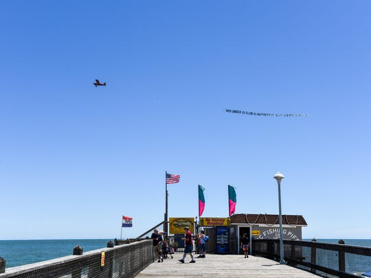 A plane flying an advertisement banner flies over the pier at Ocean City beach on Monday.