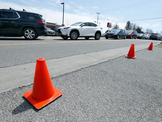 Cones keep traffic away from a driveway as cars on