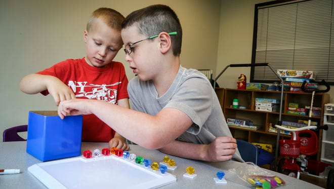 Sidney Trees, 8, right, teaches a game to Caleb Van Wyk. Sidney is receiving therapy for autism, and the treatment is being paid for by the state.