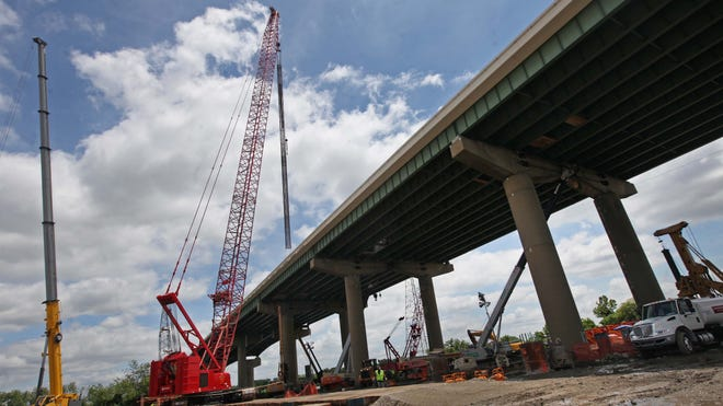 A crane lowers a 150-foot piece of caging through a 6-by-6-foot hole in the southbound lane of the I-495 bridge over the Christina River, Thursday, June 25, 2014.