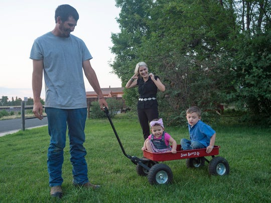 Cody and Sierra Briggs play with two of their children,