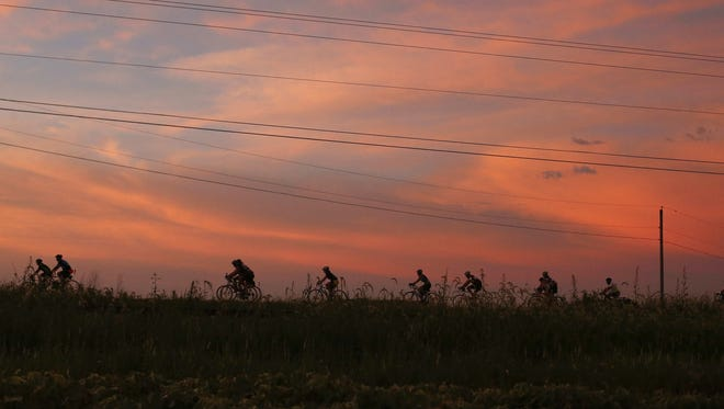 Riders pedal along to Essex as the early morning sunrise colors the clouds orange during RAGBRAI on Monday, July 25, 2016.