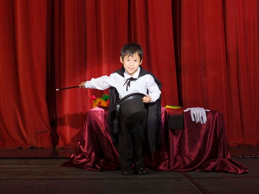 Boy doing magic trick on stage