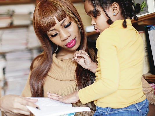 Mother and daughter reading together in library.