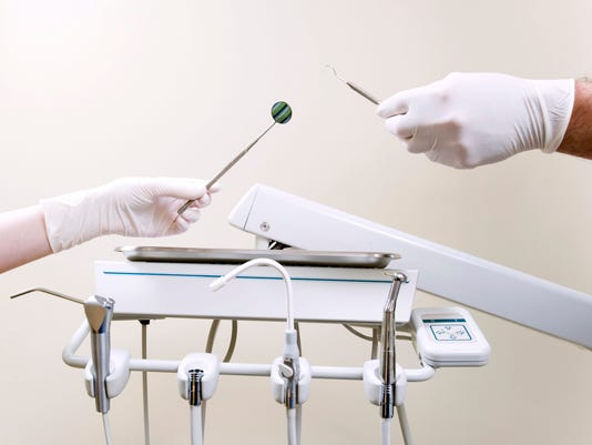 Two people's hands holding exam tools by tray of dental equipment