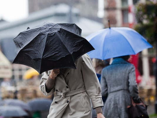 people with umbrellas walking in the city