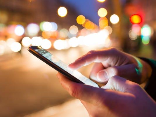 Man using his Mobile Phone in the street, bokeh