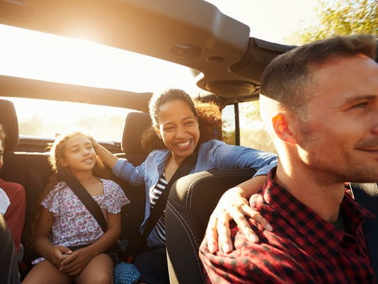 Happy family on a road trip in car, front passenger