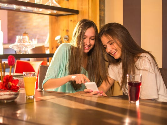 Two young teenage girl using phone while having a drink together in bar.