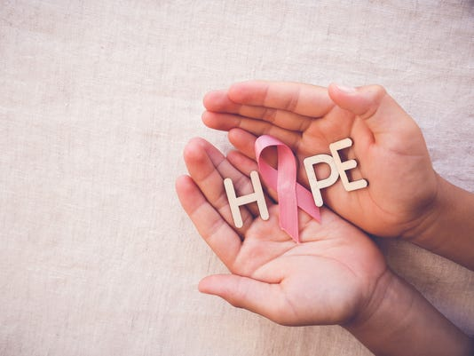 Pink Ribbon and HOPE word on hands, Breast cancer awareness